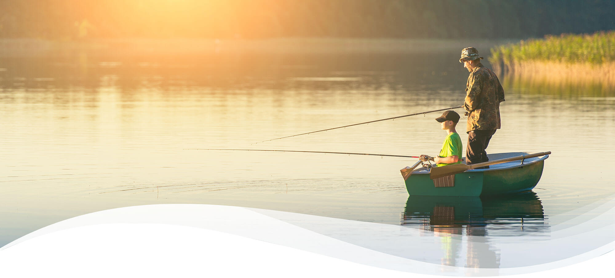 Father and son fishing in a small green row boat at sunrise